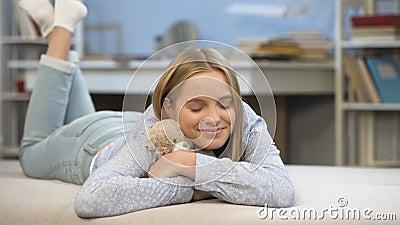 Glimlachend schoolmeisje die haar teddybeerstuk speelgoed in slaapkamer, het comfort van het kinderjarenhuis koesteren stock videobeelden