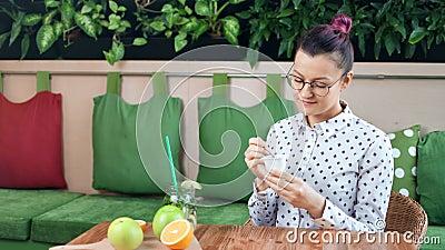 Glimlachend toevallig jong meisje die op dieet verse yoghurtzitting op lijst in koffie middelgroot schot eten stock footage