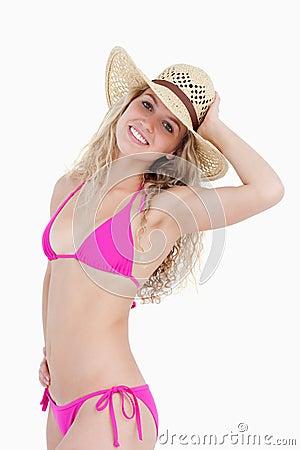 Glimlachende blondetiener die haar hoed houden