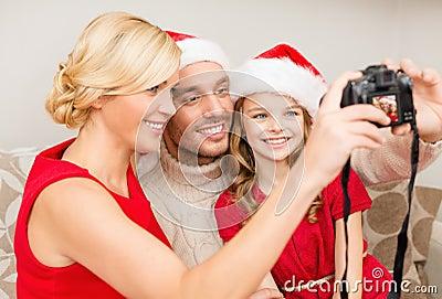 Glimlachende familie in de hoeden die van de santahelper beeld nemen
