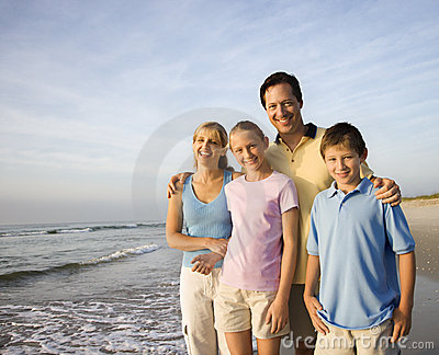 Glimlachende familie op strand.