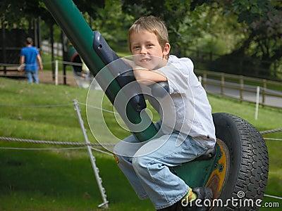 Glimlachende gelukkige jongen die op grote rotatie-schommeling rust