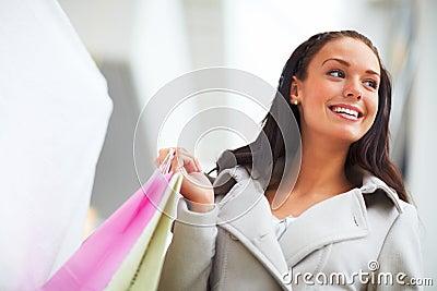 Glimlachende jonge dame dragende het winkelen zakken