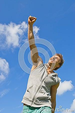 Glimlachende jonge mens met zijn wapen dat in vreugde wordt opgeheven