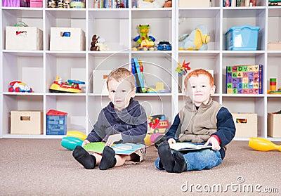 Glimlachende kinderen die jonge geitjesboeken in spelruimte lezen