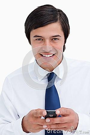 Glimlachende kleinhandelaar die zijn cellphone houdt