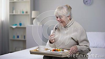 Glimlachende oude vrouw die diner in verpleeghuis, sociale zekerheid voor oude mensen eten stock videobeelden