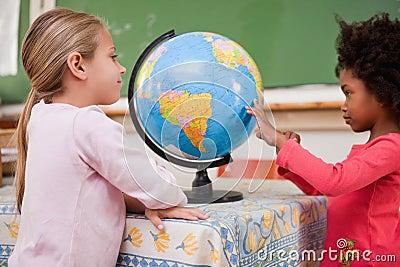Glimlachende schoolmeisjes die een bol bekijken
