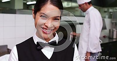Glimlachende serveerster die een schotel worden overhandigd door chef-kok stock video