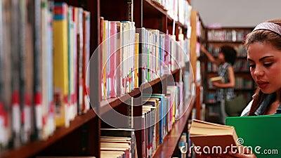 Glimlachende student die een handboek in bibliotheek uitkiezen stock footage