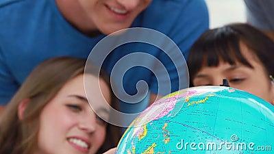 Glimlachende studenten die de wereld op een bol bekijken stock video