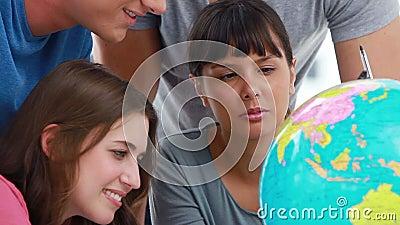 Glimlachende studenten die op landen op een bol richten stock footage