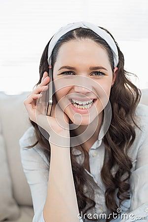 Glimlachende toevallige vrouw die een telefoongesprek hebben