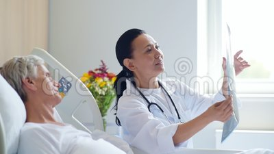 Glimlachende vrouw arts die x ray aftasten bespreken met haar oude patiënt stock footage