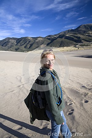 Glimlachende Wandelende vrouw op zand