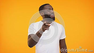Glimlachende zwarte mens die vinger richten, die bewust tegen gele achtergrond knipogen stock videobeelden