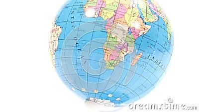 Globe en plastique coloré Inclinez du fond blanc au-dessus de l'Afrique au fond blanc banque de vidéos