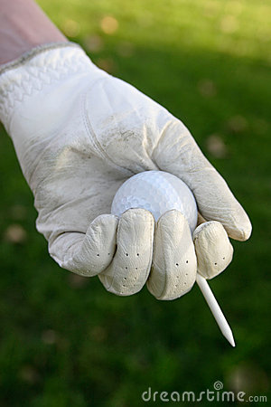 Glove on hand holding golf ball and tee