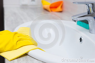 Gloved hand cleaning sink edge Stock Photo
