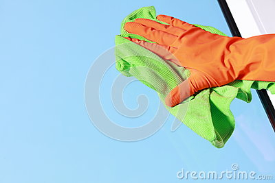 Gloved hand cleaning window with rag