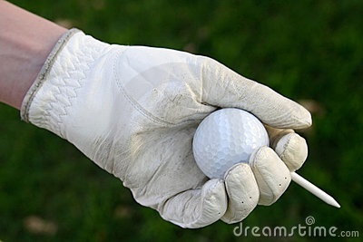 Gloved hand holding golf ball with tee