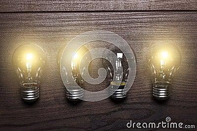 Glowing bulbs weak link concept on wooden