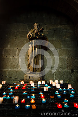 Glowing candles in front of a church statue