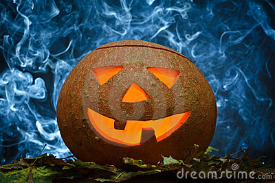 Glowing halloween pumpkin and blue smoke