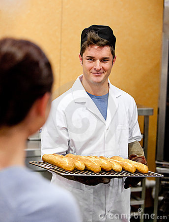 Glowing young male baker holding baguettes