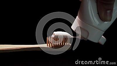 Gnieść Białą pastę do zębów na Tradycyjnym Eco Życzliwym Drewnianym Bambusowym Toothbrush na Czarnym tle zbiory wideo