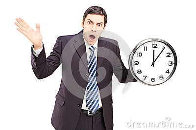 Gniewny mężczyzna trzyma gestykulować i zegar w kostiumu