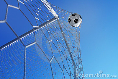 Goal. Soccer ball in net on blue sky background.