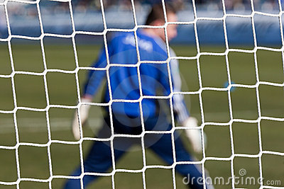 Goalkeeper behind football net