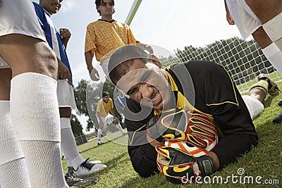 Goalkeeper on ground holding soccer ball