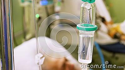 Gocciolamento endovenoso in ICU con il paziente su fondo video d archivio