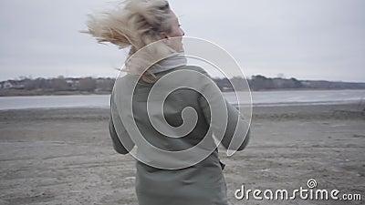 Goedaardige blanke blonde vrouw die ronddraait aan de oever van het meer of de rivier Blij dat meisje buitenshuis plezier doet stock videobeelden