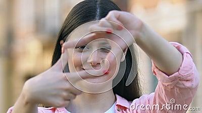 Goedgelovige vrouw die met vingers een frame heeft, fotograaf die de hoek van de camera kiest stock video
