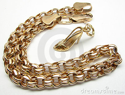 Gold bracelet and high heel shoe