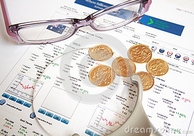 Gold coins with eyeglasses and magnifier