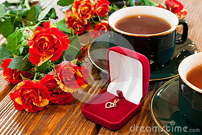 Gold jewelry, cups of tea and roses bouquet