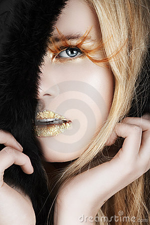Gold leaf and false eyelashes on a blond woman