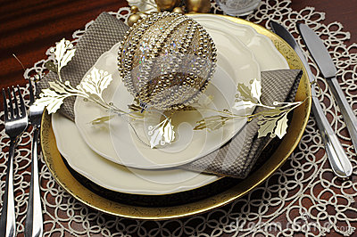 Gold metallic theme Christmas  formal dinner table place setting. Close up.