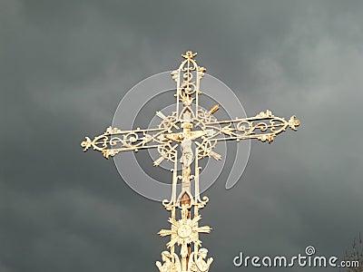 Gold ornate cross on dark sky