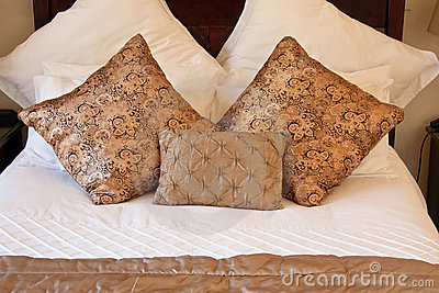 Gold pillows on white bed
