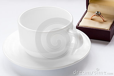 Gold ring with a diamond and a cup and saucer