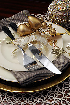 Gold theme Christmas dinner table setting. Close up on cutlery and plates