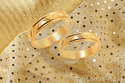 Gold wedding rings on golden festive background