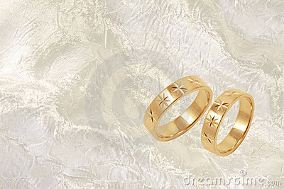 Gold wedding rings on white festive background