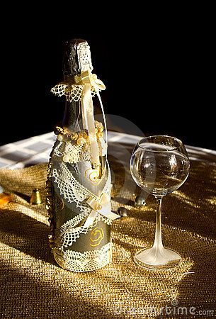 Golden bottle champaign and empty goblet