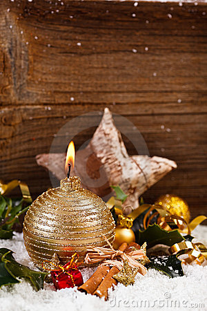 Golden candle and christmas decoration in snow